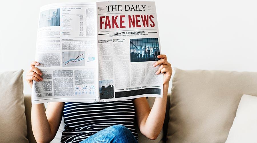 noia mirant un diari que es titula fake nwes