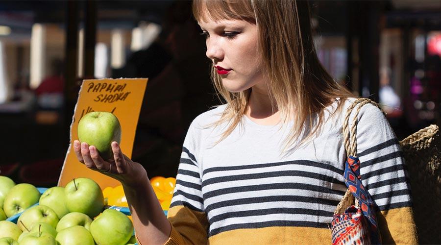 Una noia es mira una poma