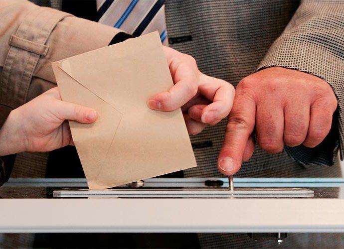 Un elector diposita el vot en una urna
