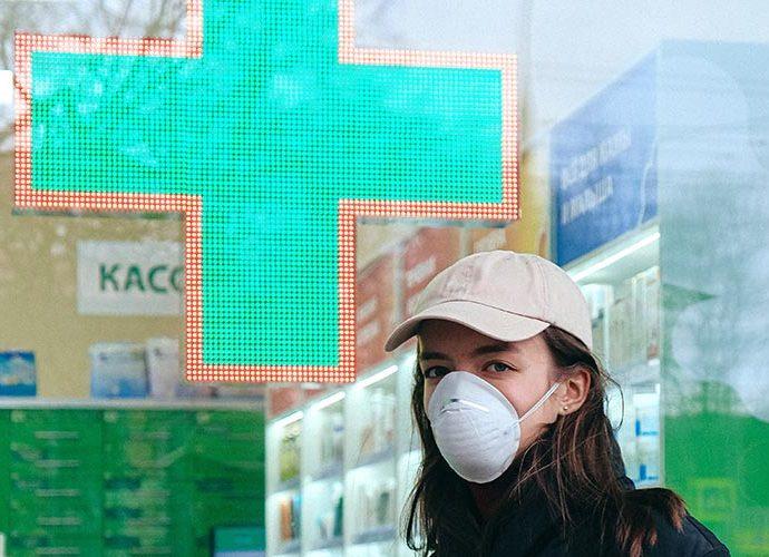 Una dona amb mascareta davant d'una farmàcia