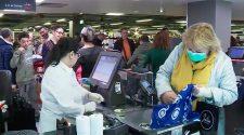 Una senyora amb mascareta fent la compra en un dia de molta afluència als supermercats.