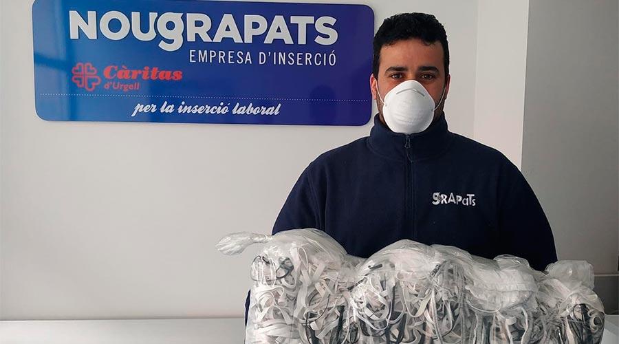 Un home carrega un paquet de mascaretes casolanes acabades de desinfectar