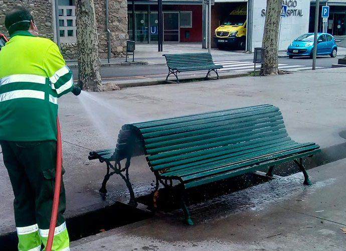 UN operari desinfecta un banc a la Seu d'Urgell