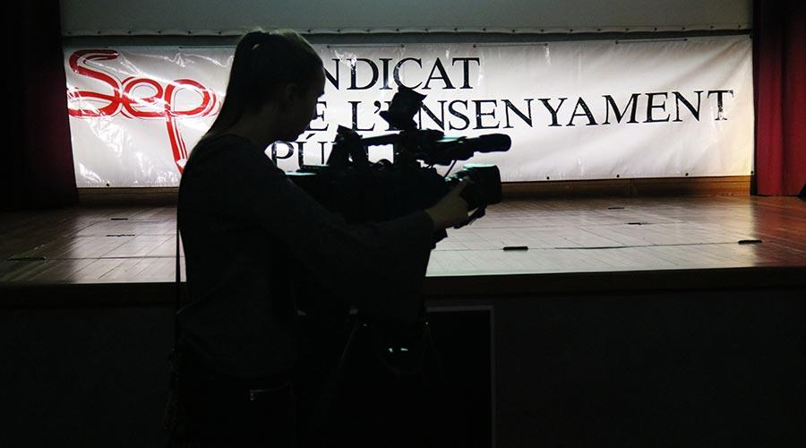 Una càmera de televisió davant la pancarta del Sindicat d'Ensenyament Públic