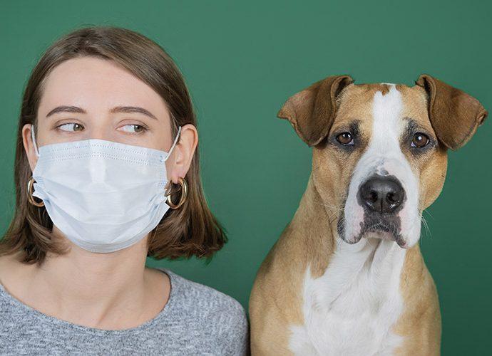 Noia amb mascareta i un gos