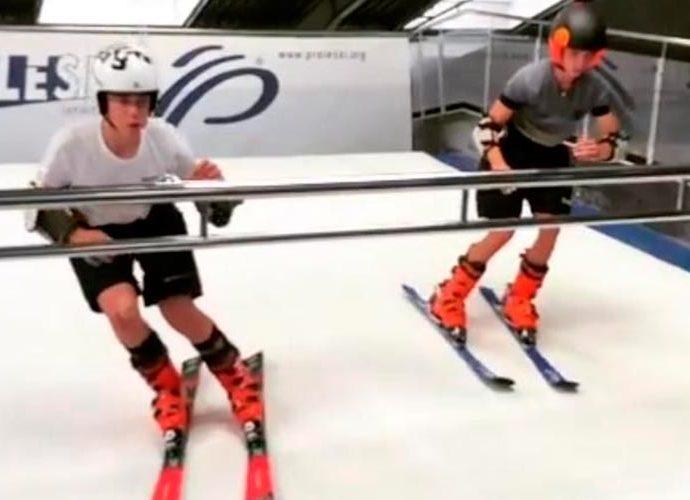 Dos joves practiquen al simulador d'esquí