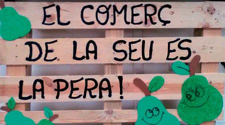 """Imatge d'una campanya de la unió de botiguers de la Seu d'Urgell on es llegeix """"El Comerç de la Seu és la Pera!"""" escrit en un palet on hi ha peres dibuixades"""