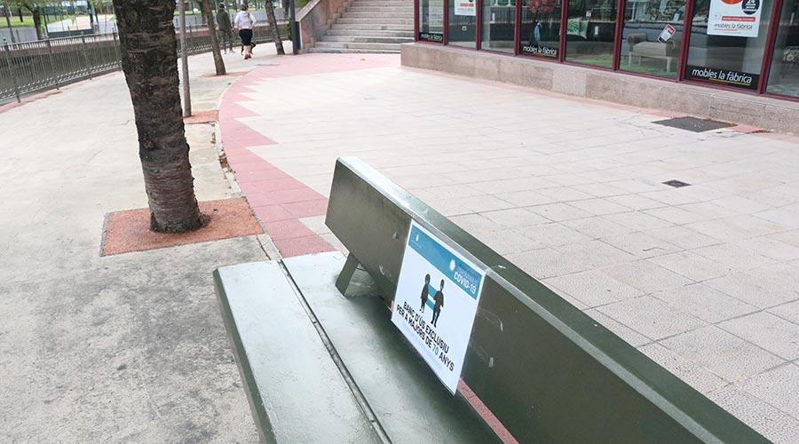 Un banc al passeig del riu a Andorra la Vella amb el cartell de l'emergència sanitària per la Covid-19