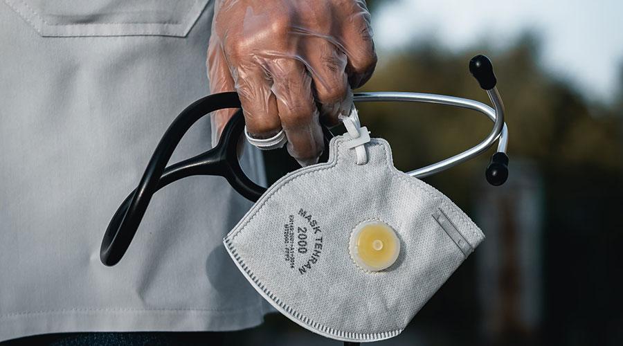 Un sanitari amb estetoscopi, guants i mascareta