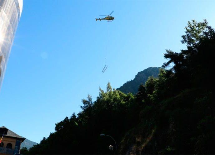 Un helicòpter s'endú una part d'una torre de mitja tensió davant l'edifici de FEDA