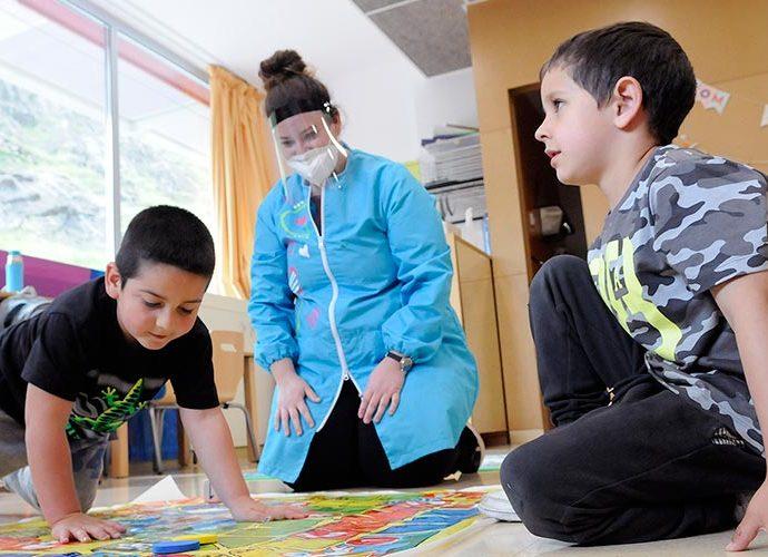 Dos escolars juguen i una educadora, protegida amb mascareta, els observa