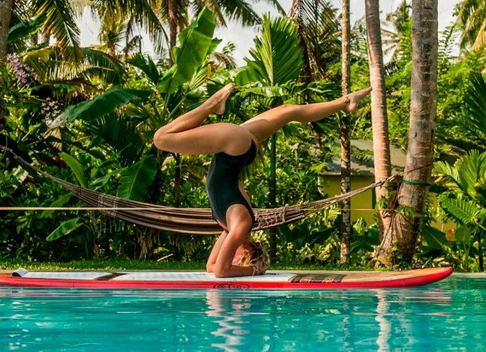 Una model fa ioga damunt una taula de surf