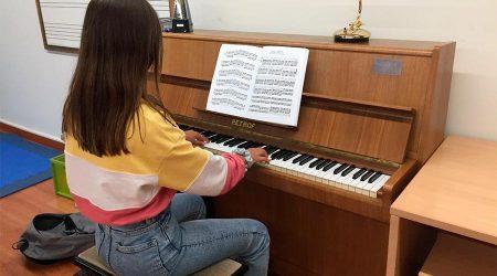 Una jove toca el piano a l'Escola de Música Municipal de la Seu d'Urgell