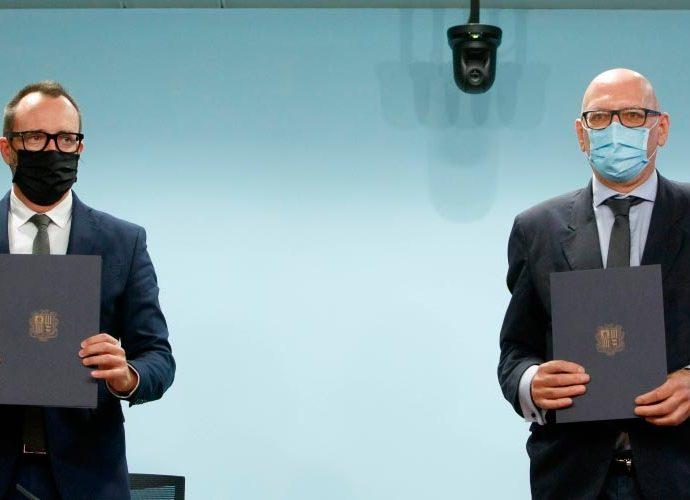 El ministre d'Afers Socials, Habitatge i Joventut, Víctor Filloy, i el rector de la Universitat d'Andorra (UdA), Miquel Nicolau, mostren unes carpetes amb l'escut del Govern