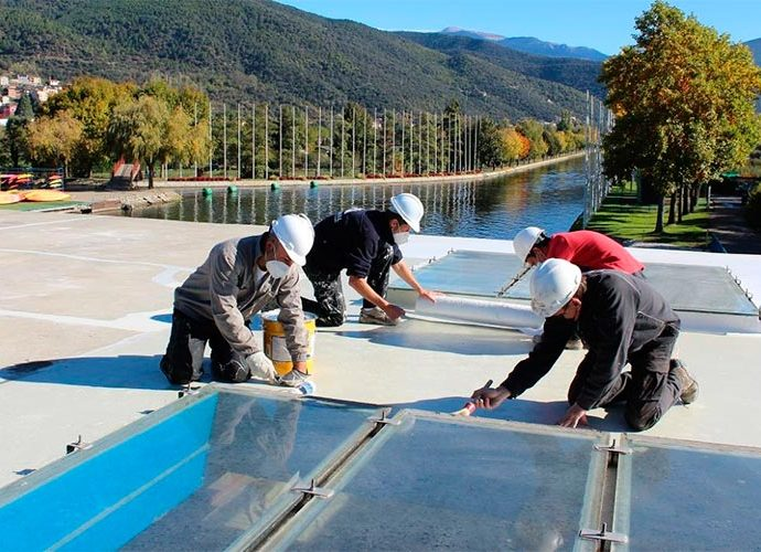 Quatre operaris treballant a la coberta de l'edifici del Parc Olímpic del Segre de la Seu d'Urgell