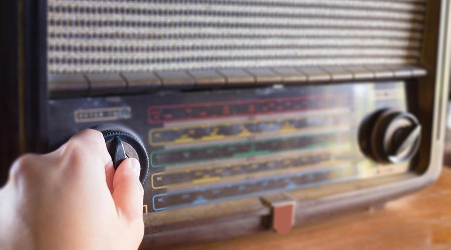 Una mà sintonitza un aparell de ràdio antic